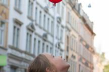 Kind schaut fliegendem Jubiläumsluftballon nach.